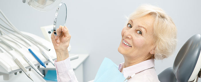 older lady in dental chair with mirror